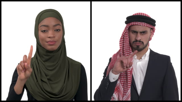 Vertical collage of two multiethnic people wearing traditional headwear expressing Rejection , No, Stop sign using index finger. Body language concept