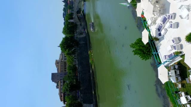 Vertical footage of Rome river Tiber with boat sailing near bridge Vittorio Emanuele II, aerial