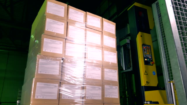 A vertical machine covering rotating boxes with wrap. video