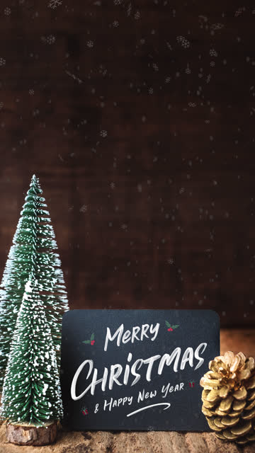 vídeos de stock e filmes b-roll de vertical merry christmas and happy new year brush stroke writing on blackboad with xmas tree and snow falling on grunge wood table and dark brown wooden wall.winter holiday greeting card - vertical