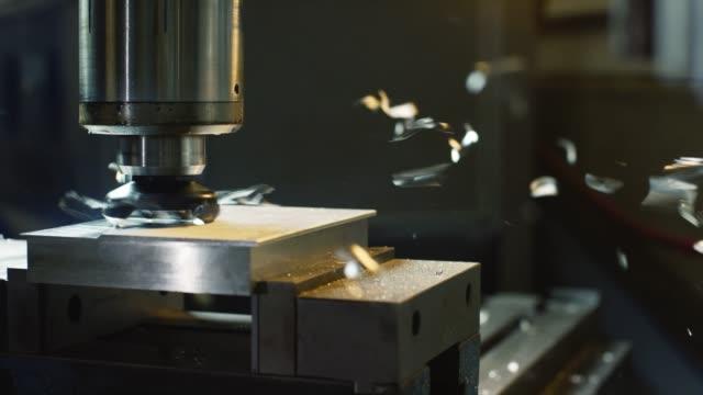 en vertikal fräs maskin nedskärningar genom aluminium som metall skärvor flyga genom luften i en inomhus tillverkningsenhet - cnc maskin bildbanksvideor och videomaterial från bakom kulisserna