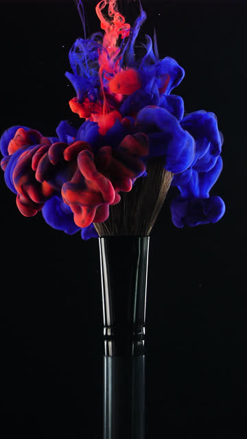 Vertical: Red and blue ink drop falling on brush with black background in slow motion Vertical video format and 4k Red and Blue ink drop falling on make up brush paint with black background painting art product stock videos & royalty-free footage