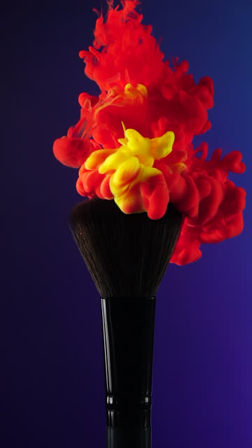 Vertical: Red and Yellow ink drop falling on brush with blue background in slow motion Vertical video format and Slow motion of Red and Yellow ink drop falling on make up brush paint with gradient blue background painting art product stock videos & royalty-free footage