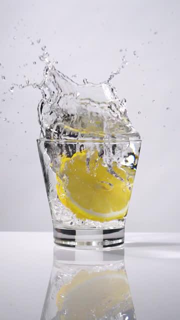 Vertical shot and Slow motion of Lemon slice splashing into glass