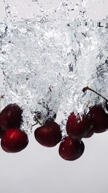 vídeos de stock e filmes b-roll de vertical slow motion: cherry drop into fresh water on white background - cereja