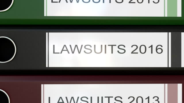 Vertical stack of multicolor office binders with Lawsuits tags 3D rendering different years video