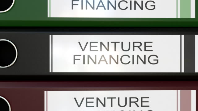Vertical stack of multicolor office binders with Venture financing tags video
