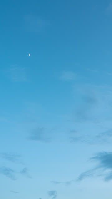vídeos de stock e filmes b-roll de vertical time lapse moon on blue sky background with clouds at twilight - vertical