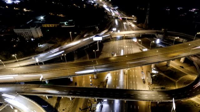 stockvideo's en b-roll-footage met verticale top-down luchtfoto van het verkeer op de snelweg interchange's nachts. - bovenkleding