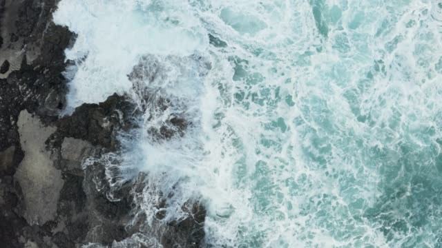 Vertical top down view of waves crashing over rocks on Lumahai beach on Kauai - video