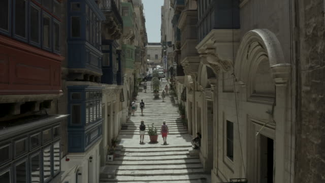 Vertical uplift, drone flying narrow beautiful old street, Valletta, Malta.Old, vintage windows, balconies, people going up stairs Vertical uplift, drone flying narrow beautiful old street, Valletta, Malta. Old, vintage windows, balconies. malta stock videos & royalty-free footage