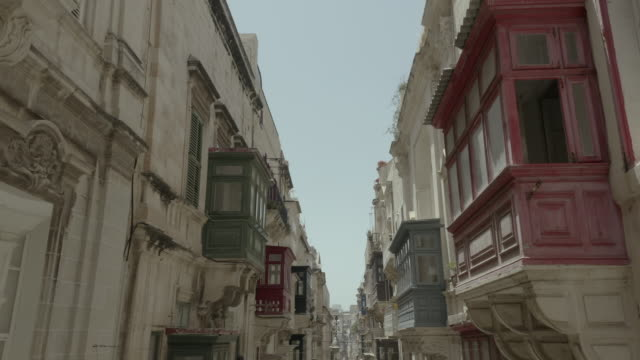 Vertical uplift, drone flying through beautiful old street, Valletta, Malta. Old, vintage balconies, road, city from top.