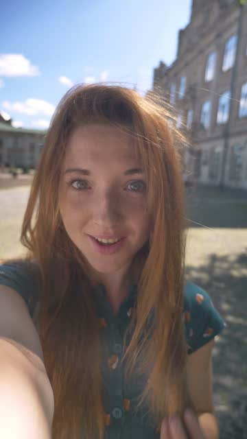 vídeos de stock e filmes b-roll de vertical video, beautiful young ginger woman taking selfie and smiling, standing on street during sunny day outdoors, happy and cheerful - vertical