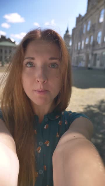 vídeos de stock e filmes b-roll de vertical video, charming ginger young woman taking selfie and touching her hair, recording video during sunny day outdoors - vertical