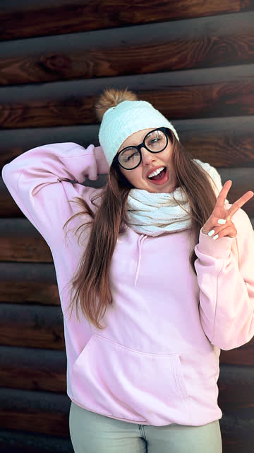 vertical video for social media. peace dudes. portrait of a joyful attractive girl in a pink blouse and a white hat. - vertical format video stock videos and b-roll footage