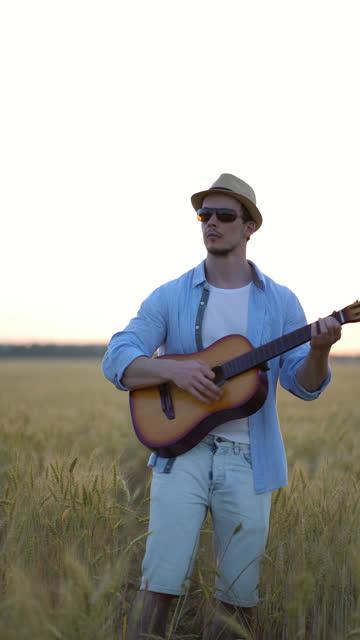 垂直ビデオ。小麦畑で屋外でアコースティックギターを演奏。 ビデオ