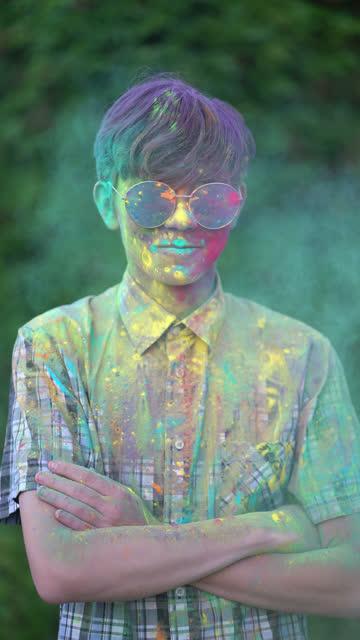 垂直ビデオ。ホーリーフェスティバルで色付きの粉末で覆われている少年の肖像画。 ビデオ
