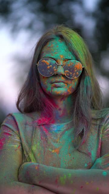 垂直ビデオ。ホーリーフェスティバルで色付きの粉末で覆われている女性の肖像画。 ビデオ