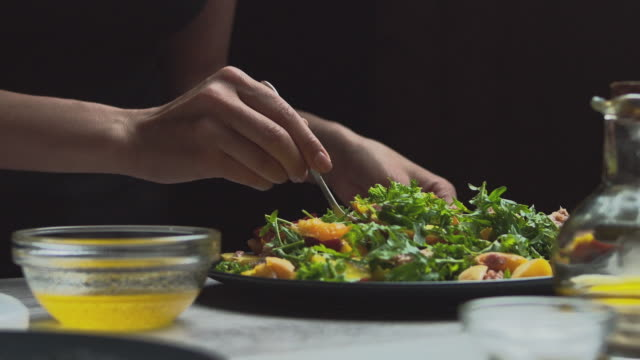 Very appetizing fruit and vegetable salad, beautiful women's hands gently mix the salad