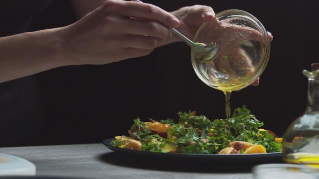 mycket aptitretande sallad, beströdd med sås, honung, olja, på bordet en svart tallrik på en mörk bakgrund. vegetarisk mat, grönsaker och frukter. - hemmagjord bildbanksvideor och videomaterial från bakom kulisserna