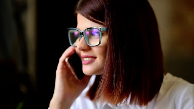 Very beautiful brunette with glasses razgovarivaet smiling using a mobile phone. Close-up video