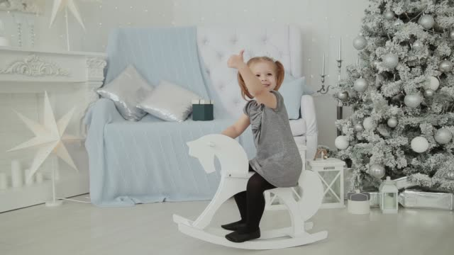 Very beautiful little girl riding on a wooden horse in the New Year's room and smiling