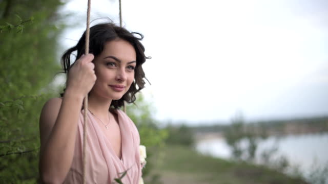Very beautiful smiling girl in light pink dress relax on the swing at the lake beach video