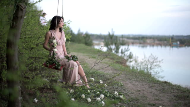Very beautiful smiling girl in light pink dress relax on the swing decorated by flowers at the lake beach video