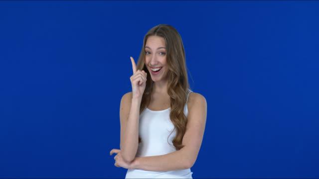 非常にかわいいとかわいい女の子は笑顔と手で警告サインを示しています. - 誘惑点の映像素材/bロール
