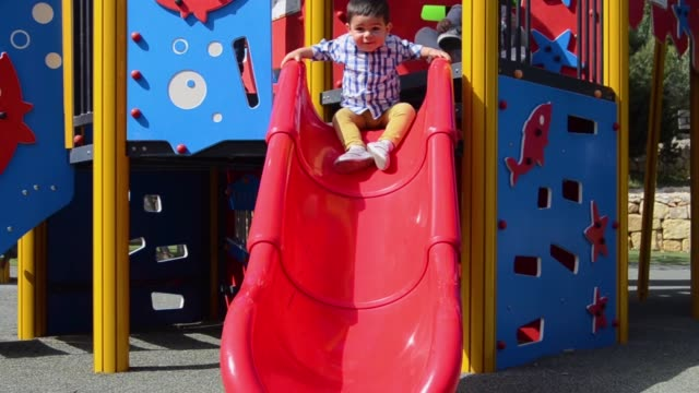 very excited boy coming down slide, early development, toddler playing in the park - scivolo video stock e b–roll