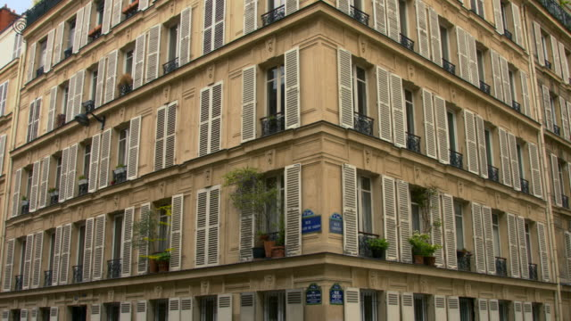 A very geometric building This building is in paris France. It looks very geometrical. It is a succession of windows, all the same. Some person put potted plants in front of their windows, the scene is calm and can be a nice establishing shot french architecture stock videos & royalty-free footage