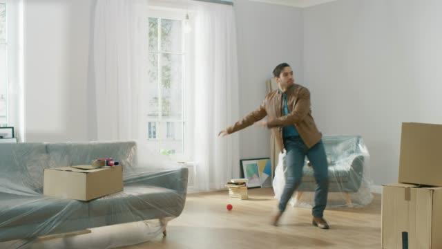 vídeos y material grabado en eventos de stock de muy alegre se muda a su nuevo apartamento, danzas emocionado. chico compró nueva página lista para inicio desembalaje de cajas de cartón. - propiedad inmobiliaria