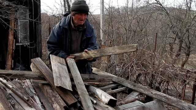 A very old man goes through the boards for repairing a hut or kindling fire, life after the war - video
