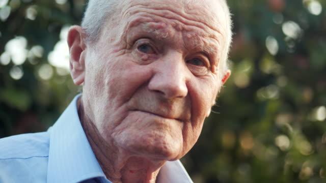 vidéos et rushes de très vieil homme portrait d'émotions. grand-père est souriant et à la recherche d'appareil photo. portrait: âgés, personnes âgées, senior. gros plan du vieil homme assis seul à l'extérieur. mouvement lent. 4k - grand père