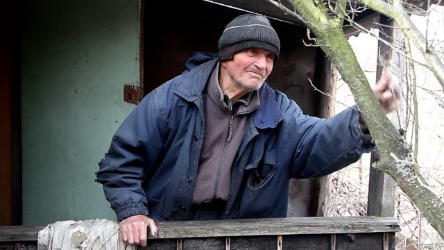 A very old sick man treats garden trees in the spring before flowering from the porch of his house. - video