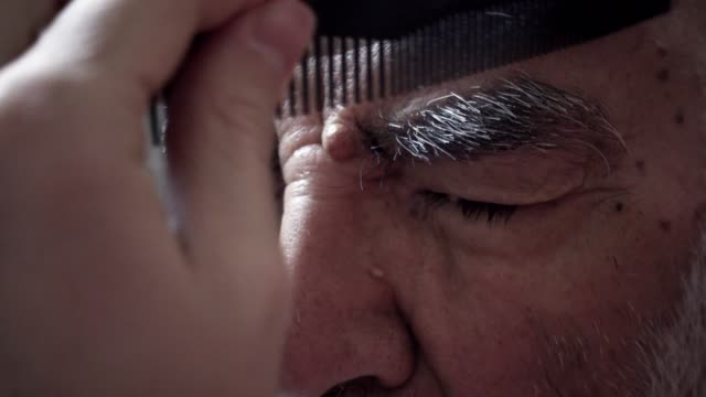 vídeos de stock e filmes b-roll de very old turkish muslim grandfather having his eyebrows trimmed by his grandson in his vintage bathroom designed in 1980's - sobrancelha