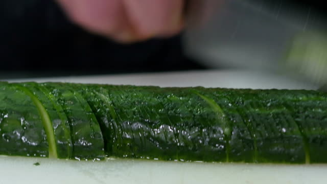 very quickly the hands of the cook cut cucumber - articoli casalinghi video stock e b–roll