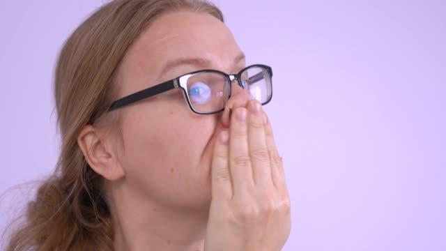 vidéos et rushes de la jeune femme très fatiguée portant des lunettes fait le geste de nettoyer son front et d'aller chercher son souffle. concept de travailler dur, les tâches ménagères ou tout autre travail épuisant. intérieur, fond lilas. - sourcils