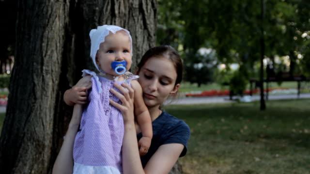 Una niñera muy joven con una muchacha del bebé con un chupete en su regazo - vídeo