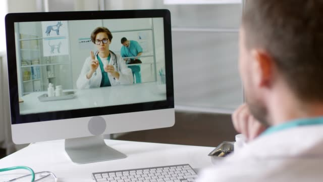 Vet Video Calling Colleague Over the shoulder shot with rack focus of male veterinarian sitting at his desk and talking on video call with female colleague showing him bottles of prescription drugs and explaining something veterinarian stock videos & royalty-free footage