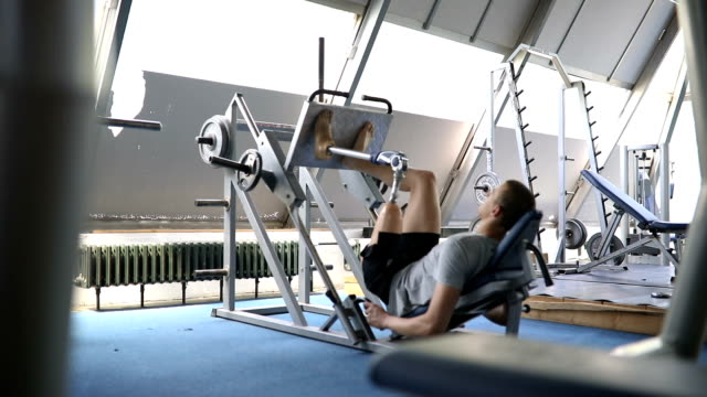 Veteran in the gym doing a leg press Amputee athlete with artificial leg, living the healthy lifestyle, exercising in the gym. artificial limb stock videos & royalty-free footage