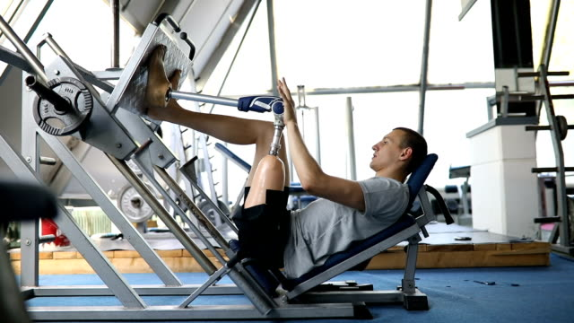 Veteran in the gym pushing a leg press Amputee athlete with artificial leg, living the healthy lifestyle, exercising in the gym. artificial limb stock videos & royalty-free footage