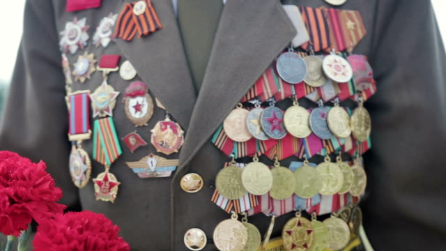 veteran of the great patriotic war and world war ii in uniform with many badges and orders comes with red flowers. close-up - rispetto video stock e b–roll