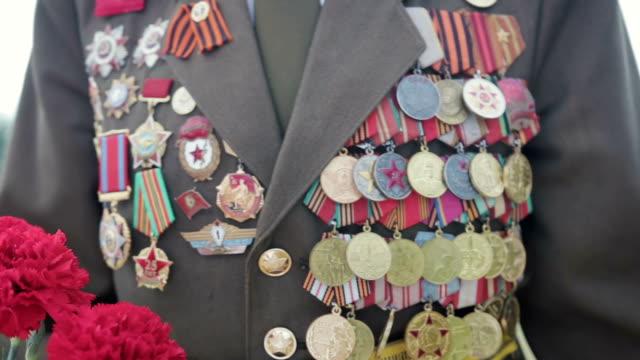 多くのバッジと注文制服大祖国戦争と第二次世界大戦のベテランは、赤い花が付属します。クローズ アップ - メダル点の映像素材/bロール