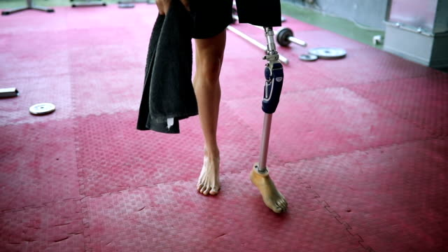 Veteran walking in the gym Amputee athlete with artificial leg, living the healthy lifestyle, exercising in the gym. amputee stock videos & royalty-free footage