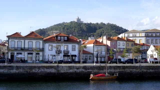 vídeos de stock e filmes b-roll de viana do castelo city viewed from the other side of the river with boats and santa luzia chruch sanctuary on the hill, in portugal - viana do castelo