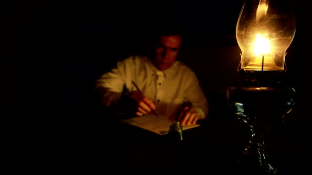 Victorian businessman writing at his desk A man lit from the light of an oil lamp dips his pen in an inkwell and begins writing. Focus on flame of oil lamp. 19th century style stock videos & royalty-free footage