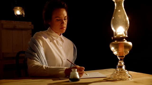 victorian era woman thinking about a letter she is writing A pensive woman from the era of the early American west writes a letter with a dip pen by the light of an old oil lamp 19th century style stock videos & royalty-free footage