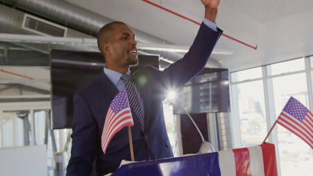 Victorious male speaker at political convention Side view close up of a smiling young African American man standing on a podium decorated with a US flag shouting and raising his fist in triumph at a political rally president stock videos & royalty-free footage