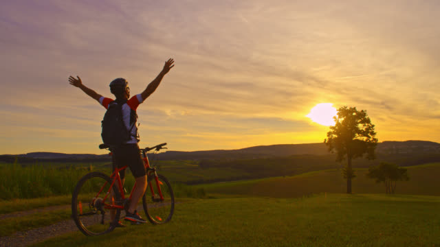 slo mo victorious mountain biker punching the air on the top of a hill - percorso per bicicletta video stock e b–roll